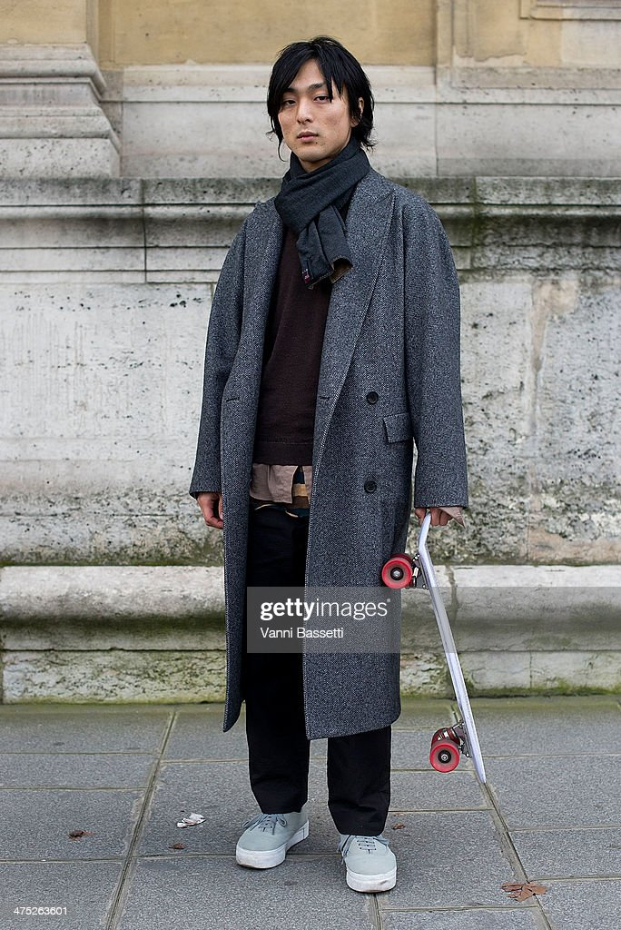 Designer Kei Toyoshima poses with a Wooyoungmi Coat before Yang Li show on Day 2 of Paris Collections Womenswear Fall/Winter 2014-2015 at Palais des Beaux Arts on February 26, 2014 in Paris, France.