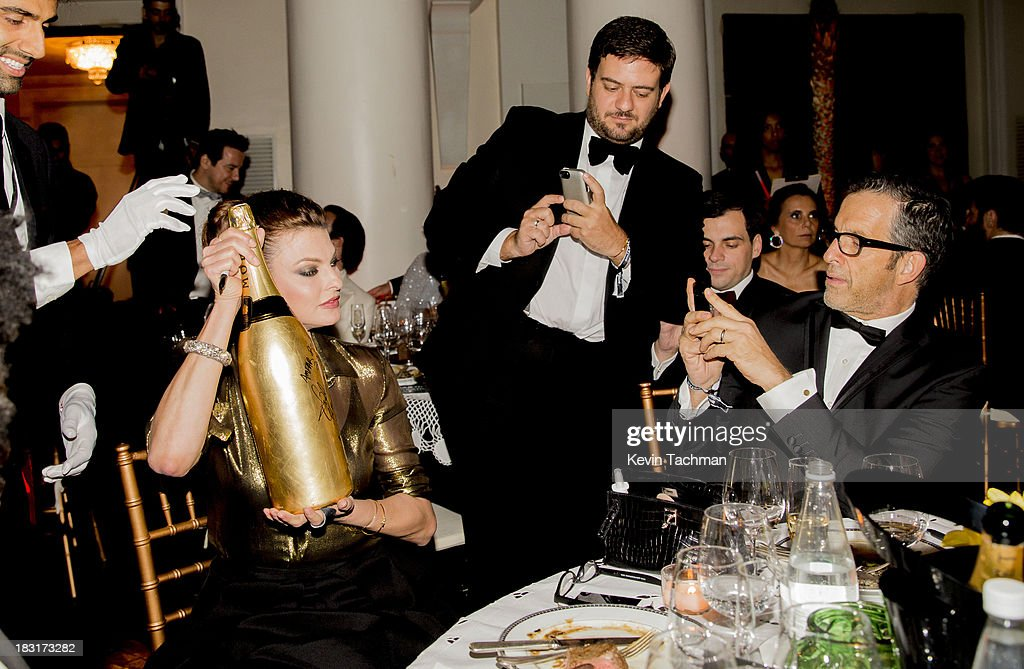 Designer Kenneth Cole, right, takes a picture of Linda Evangelista with a bottle of Moët & Chandon Impérial Gold-Leaf Jeroboam at the amfAR Inspiration Gala Rio on October 4, 2013 in Rio de Janeiro, Brazil.