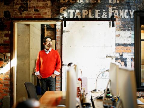 Designer leaning against door frame in office