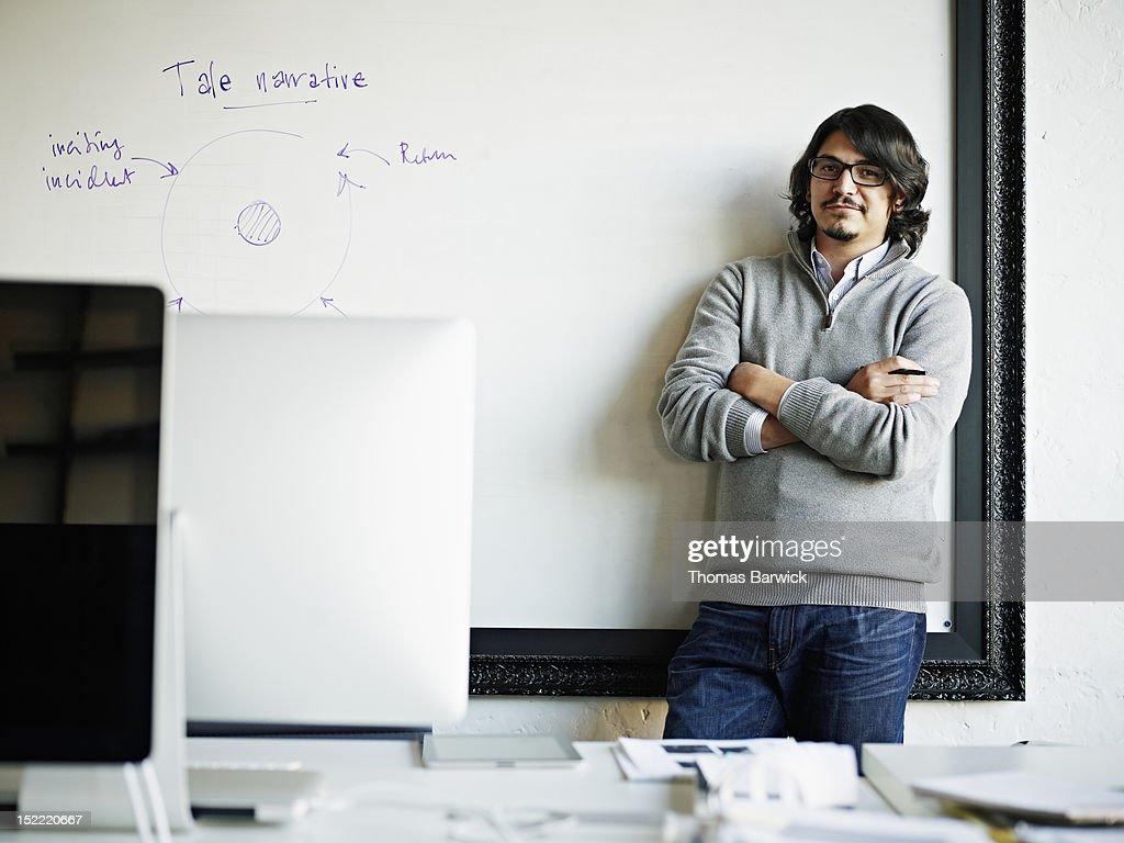 Designer leaning against white board in office : Stock Photo