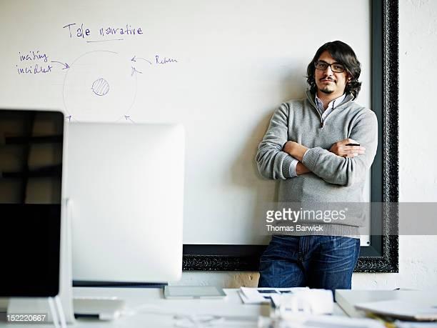 Designer leaning against white board in office