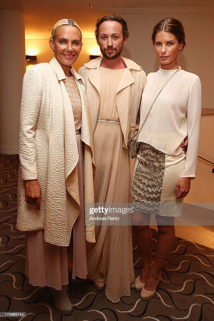 Designer Marcel Ostertag (C) and models Natascha Ochsenknecht (L) and Julia Trainer (R) prepare backstage prior to the Marcel Ostertag fashion show at Charles Hotel on July 24, 2013 in Munich, Germany.
