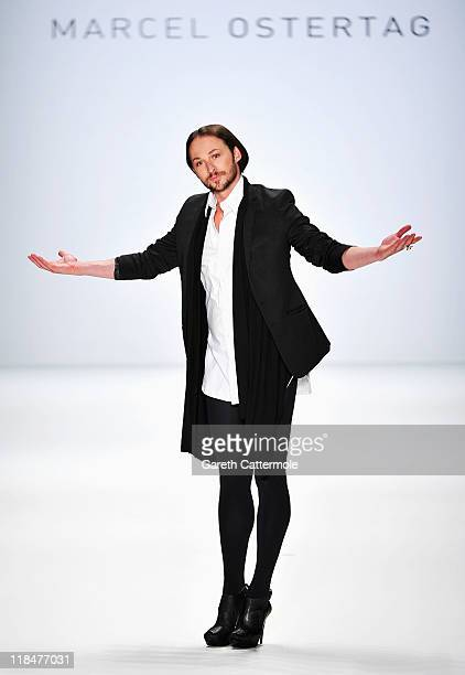 Designer Marcel Ostertag poses on the catwalk after his Show during Mercedes Benz Fashion Week Berlin Spring/Summer 2012 at the Brandenburg Gate on...