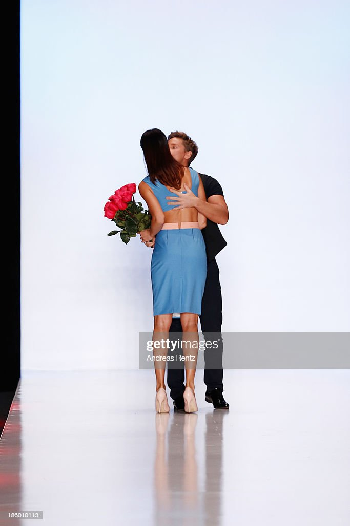 Designer Mari Axel receives flowers as she appears on the runway after the MARI AXEL show during Mercedes-Benz Fashion Week Russia S/S 2014 on October 27, 2013 in Moscow, Russia.