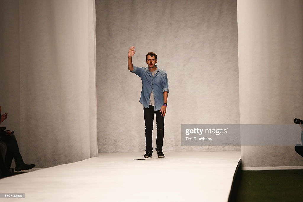 Designer Marios Schwab acknowledges the audience after the Marios Schwab show during London Fashion Week SS14 at TopShop Show Space on September 16, 2013 in London, England.