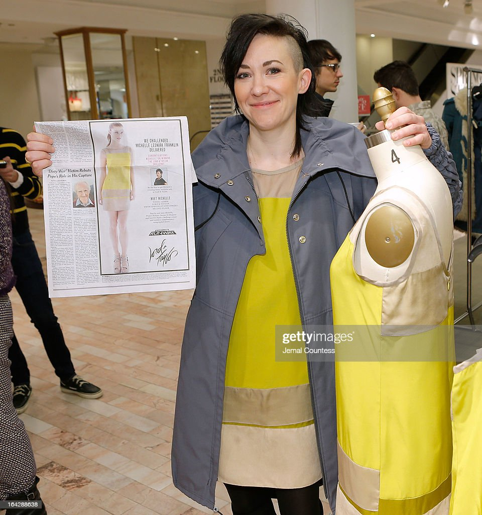Designer Michelle Franklin holds a newspaper insert as she poses with her Project Runway Lord & Taylor challenge during an in-store at the Lord & Taylor Flagship store on March 22, 2013 in New York City.