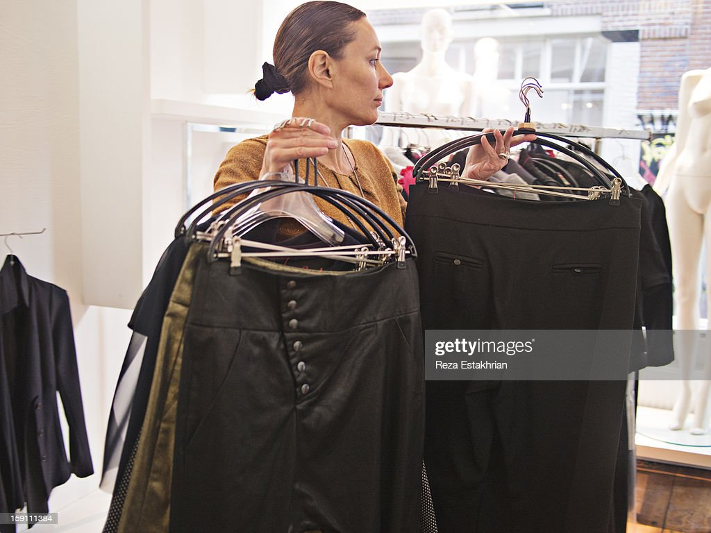 Designer moves garments to new positions : Stock Photo