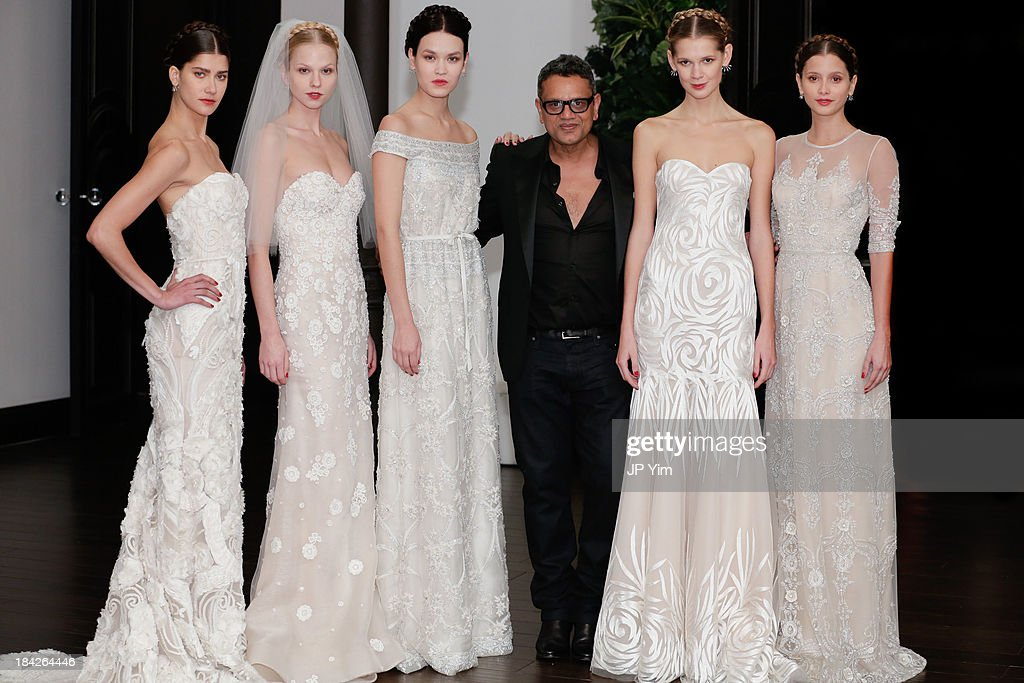 Designer Naeem Khan poses with models during his Naeem Khan Fall/Winter 2014 Bridal collection presentation and reception on October 12, 2013 in New York City.