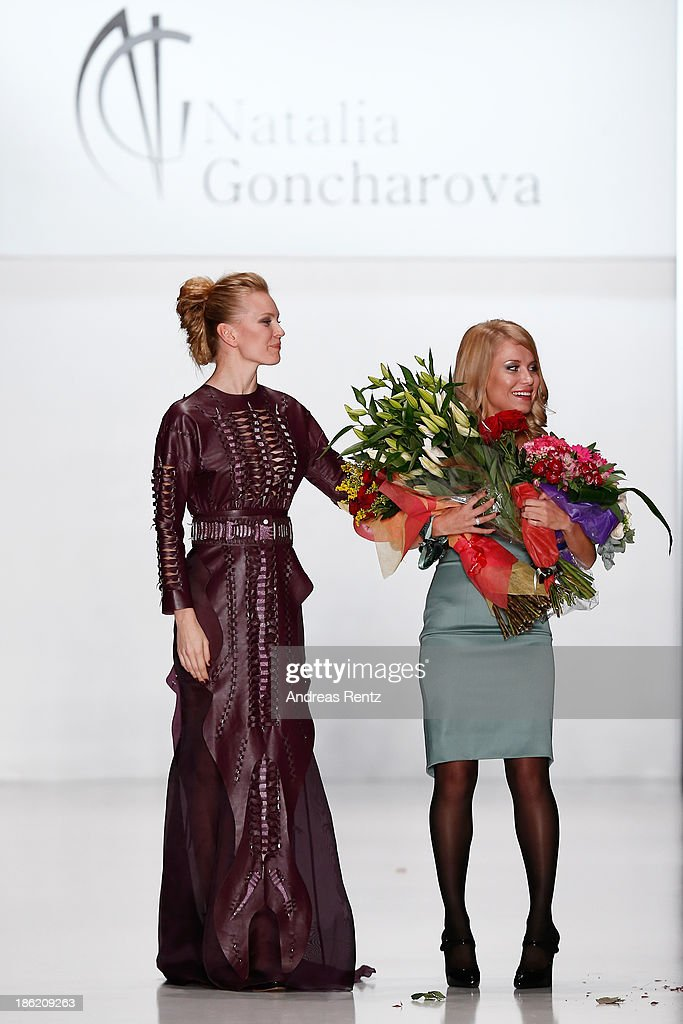 Designer Natalia Goncharova (R) receives flowers at the finale of the Natalia Goncharova show during Mercedes-Benz Fashion Week Russia S/S 2014 on October 29, 2013 in Moscow, Russia.