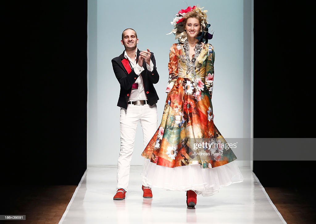 Designer Nikolai Kyvyrzhik and a model appear on stage at the Nikolai Kyvyrzhik by SLAVA ZAITSEV during Mercedes-Benz Fashion Week Russia S/S 2014 on October 31, 2013 in Moscow, Russia.