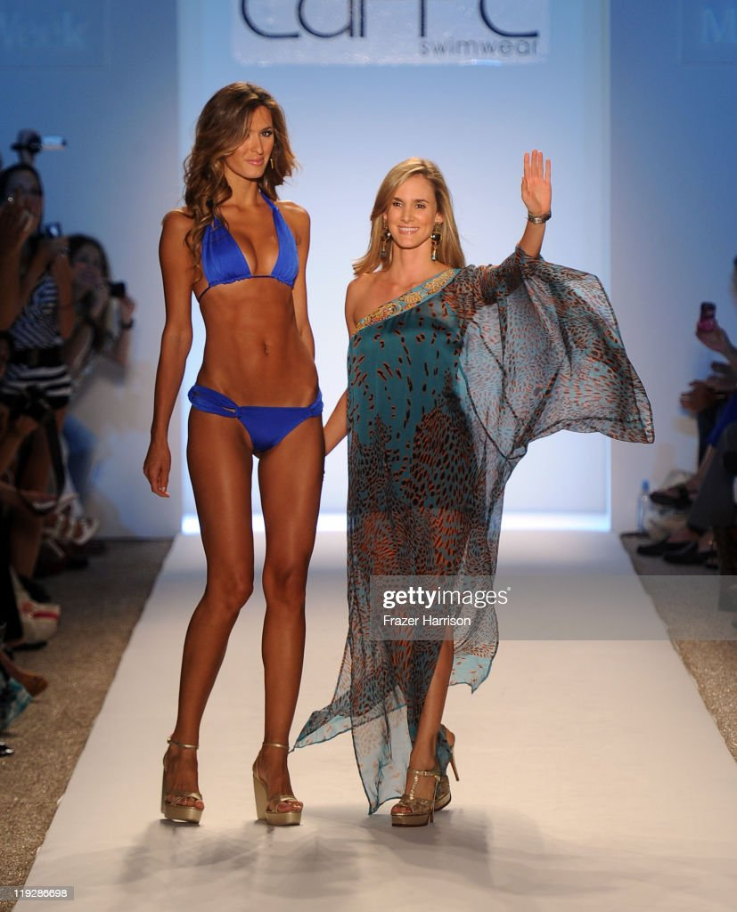 Designer Paula Saavedra walks with a model on the runway for the Caffe Swimwear show during MercedesBenz Fashion Week Swim 2012 at The Raleigh on...