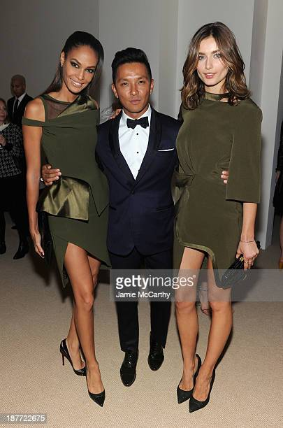 Designer Prabal Gurung poses with model Joan Smalls and guest at CFDA and Vogue 2013 Fashion Fund Finalists Celebration at Spring Studios on November...