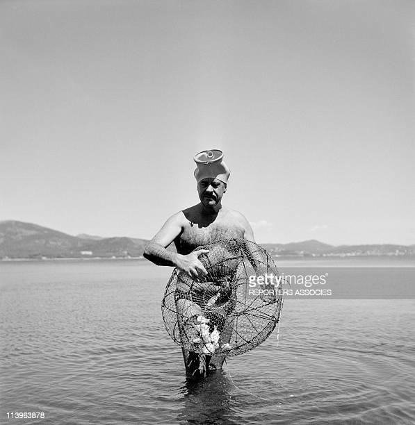Designer Raymond Loewy on holiday in Southern France with wife Viola In Saint Tropez France In 1960 Fishing on the beach