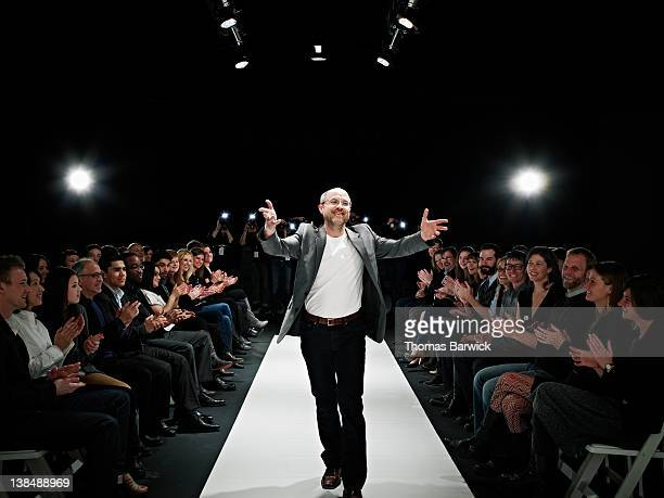 Designer receiving applause and waving to crowd