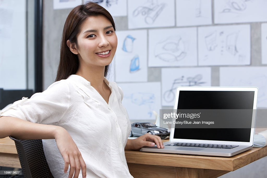 Designer sitting before laptop in studio : Stock Photo