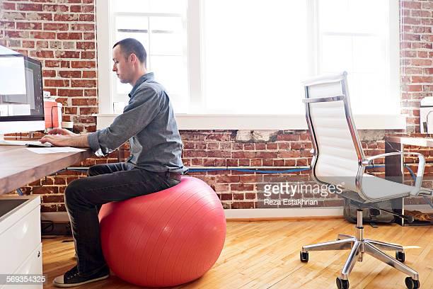 Designer sitting on balance ball at his work compu