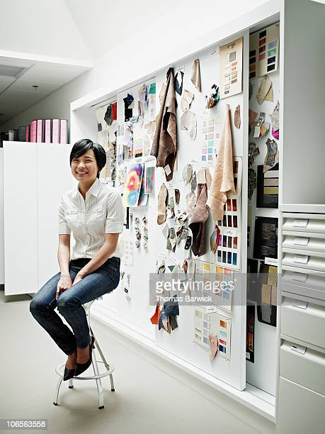 Designer sitting on stool in front of swatch board