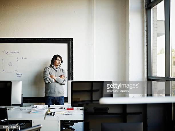 Designer standing against white board in office