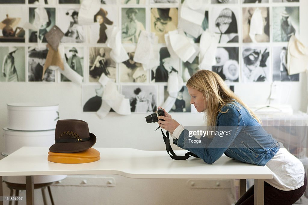 Designer taking picture of hat : Stock Photo