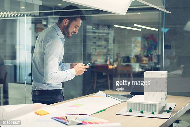 Designer typing on smart phone in office.