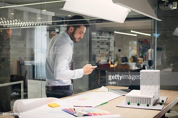 Diseñador escribiendo en el teléfono inteligente en oficina.
