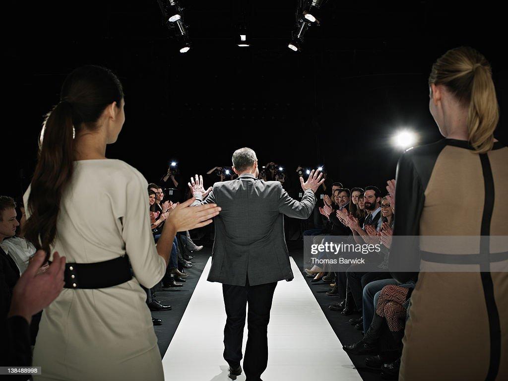 Designer walking onto catwalk at fashion show : Stock Photo