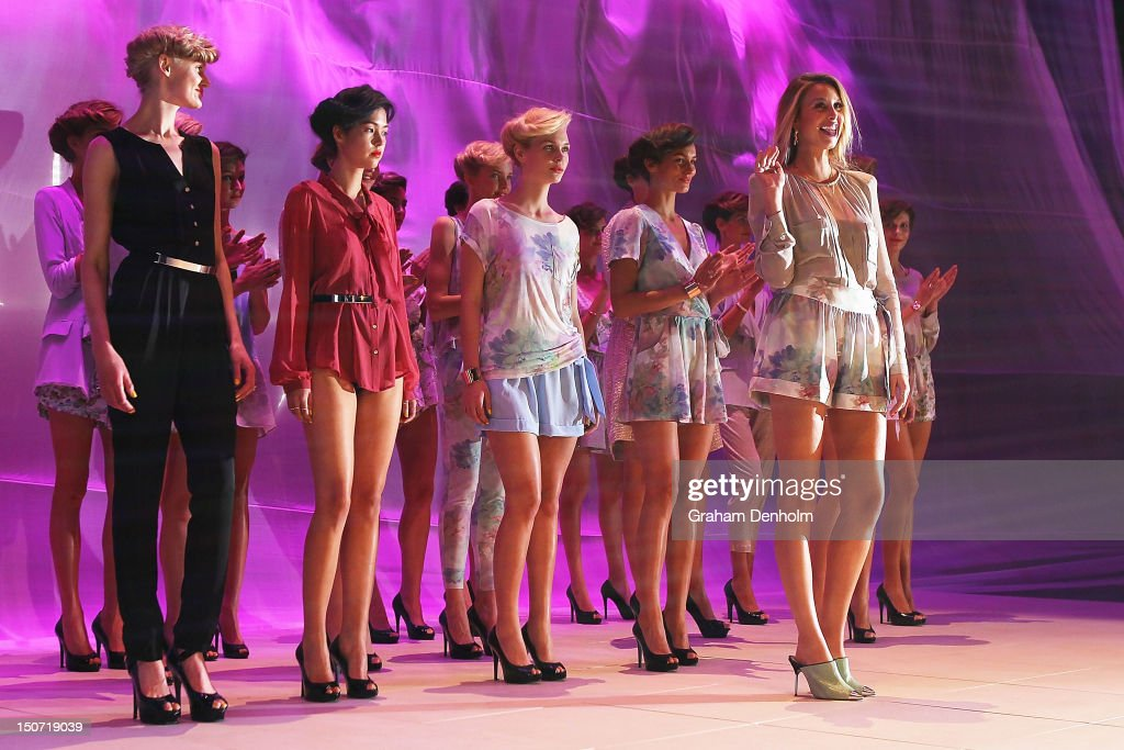 Designer Whitney Eve (R) smiles and waves on the catwalk following her collection show as part of the Mercedes-Benz Fashion festival Sydney 2012 at Sydney Town Hall on August 25, 2012 in Sydney, Australia.