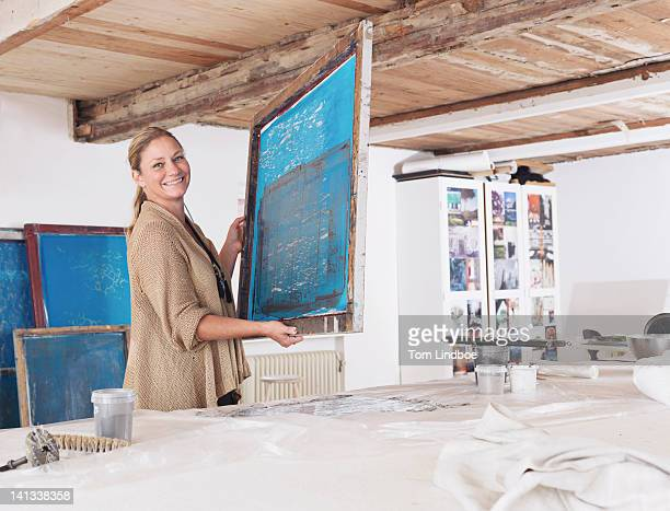 Designer with printing screen in studio