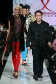 Designer Yongki Budisutisna walks the catwalk following his collection show as part of IPMI show on the fifth day of Jakarta Fashion Week 2010 at...
