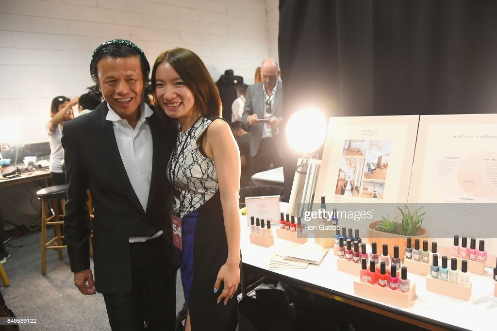 Designer Zang Toi (L) poses with Amy Ling Lin A model prepares backstage for the Zang Toi fashion show during New York Fashion Week: The Shows at Gallery 3, Skylight Clarkson Sq on September 13, 2017 in New York City.