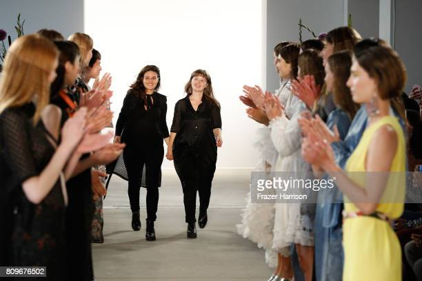 Designers Caroline Rohner and Inna Stein acknowledge the applause of the audience at the Steinrohner show during the MercedesBenz Fashion Week Berlin...