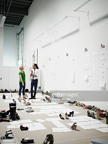 Designers discussing sample shoes and drawings