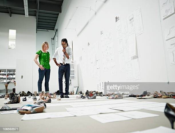 Designers examining sample shoes on floor