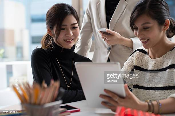 Designers have a meeting while looking at the tablet