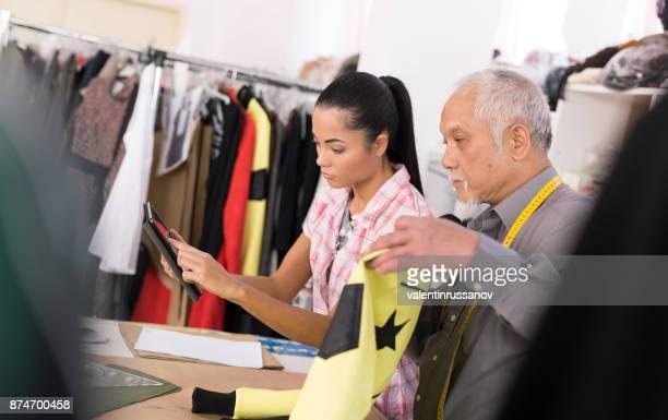 Designers in fashion studio using tablet