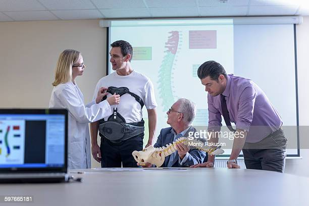 Designers in meeting discuss orthopaedic back support