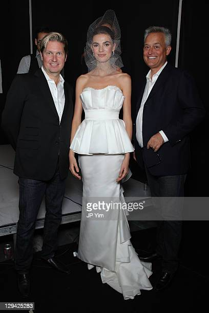 Designers James Mischka and Mark Badgley pose backstage with a model before their Badgley Mischka Bride Spring 2012 show at Pier 94 on October 16...