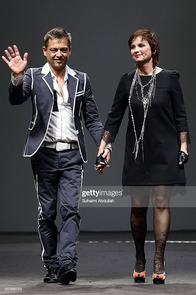 Designers Livia Stoianova (R) and Yassen Samouilov wave to the crowd after their show on closing day of French Couture Week 2012 Singapore at The Shoppes at Marina Bay Sands on December 2, 2012 in Singapore.