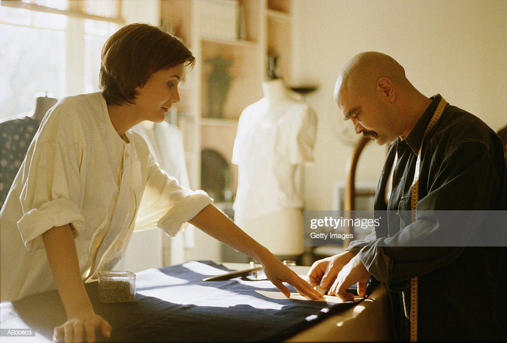 Designers marking fabric with chalk : Stock Photo