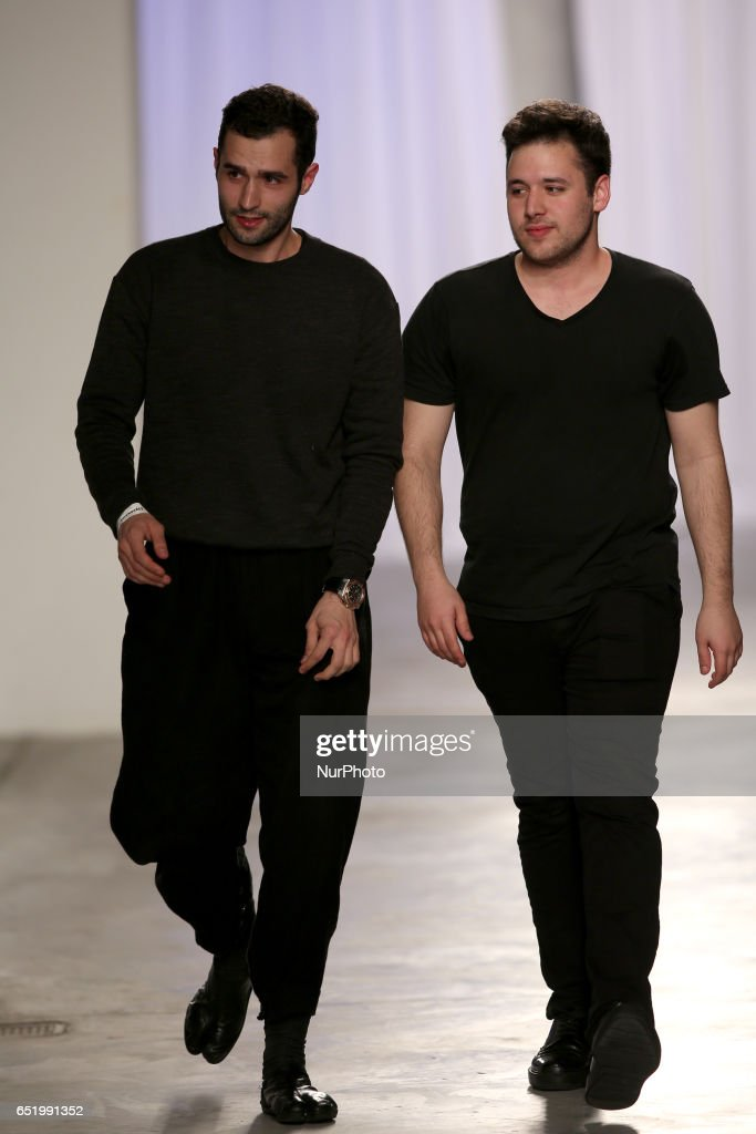 Designers Pedro Barbosa (L) and David Ferreira present a creation from the Portuguese fashion designer David Ferreira Fall/Winter 2017/2018 collection during the Lisbon Fashion Week on March 10, 2017 in Portugal.