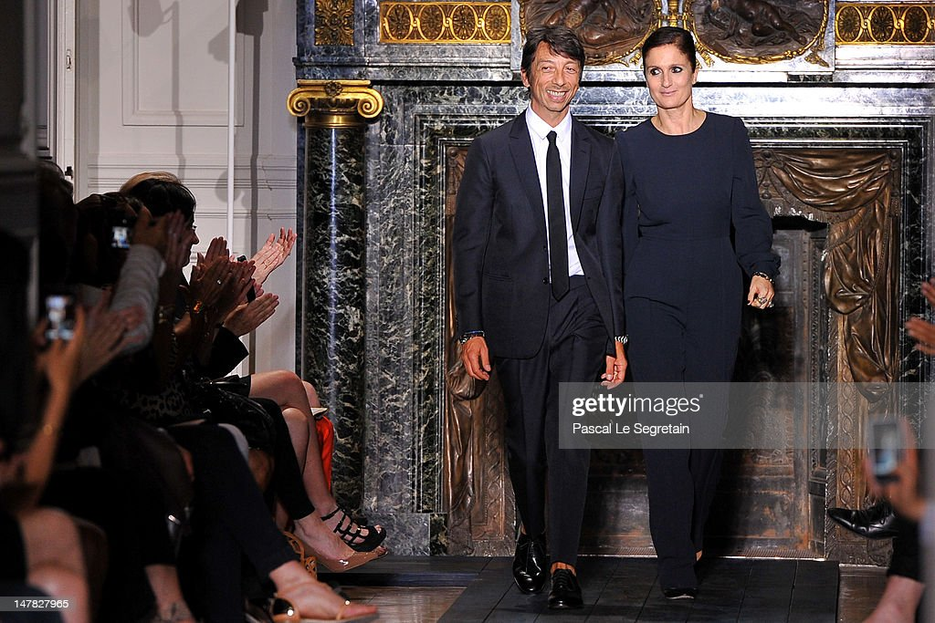 Designers <a gi-track='captionPersonalityLinkClicked' href=/galleries/search?phrase=Pier+Paolo+Piccioli&family=editorial&specificpeople=5551258 ng-click='$event.stopPropagation()'>Pier Paolo Piccioli</a> and <a gi-track='captionPersonalityLinkClicked' href=/galleries/search?phrase=Maria+Grazia+Chiuri&family=editorial&specificpeople=5551257 ng-click='$event.stopPropagation()'>Maria Grazia Chiuri</a> acknowledge the applause of the audience after the Valentino Haute-Couture show as part of Paris Fashion Week Fall / Winter 2012/13 at Hotel Salomon de Rothschild on July 4, 2012 in Paris, France.