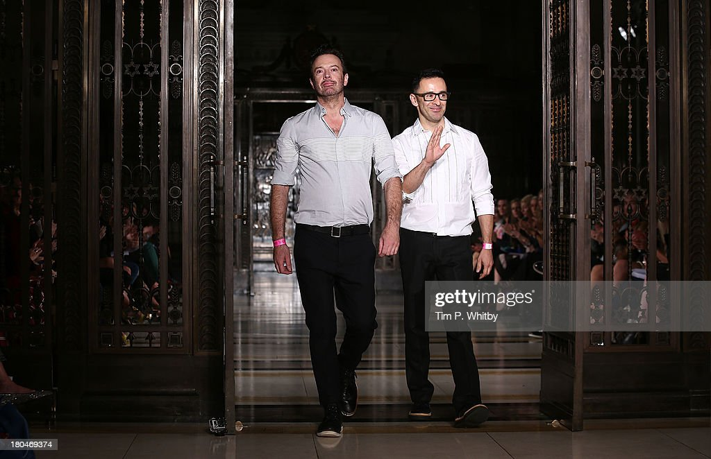 Designers Reynold Pearce and Andrew Fionda walk the runway during the Pearce Fionda show at London Fashion Week SS14 at Freemasons Hall on September 13, 2013 in London, England.
