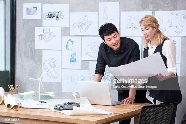 Designers studying blueprint in studio
