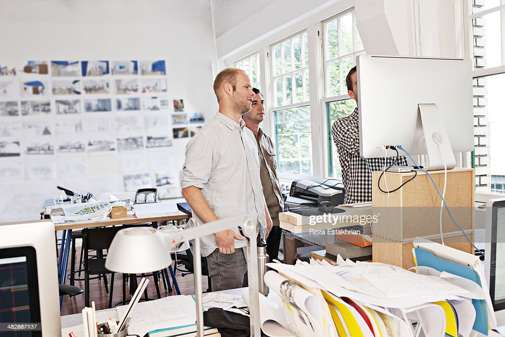 Designers talk over design issue on a computer : Stock Photo