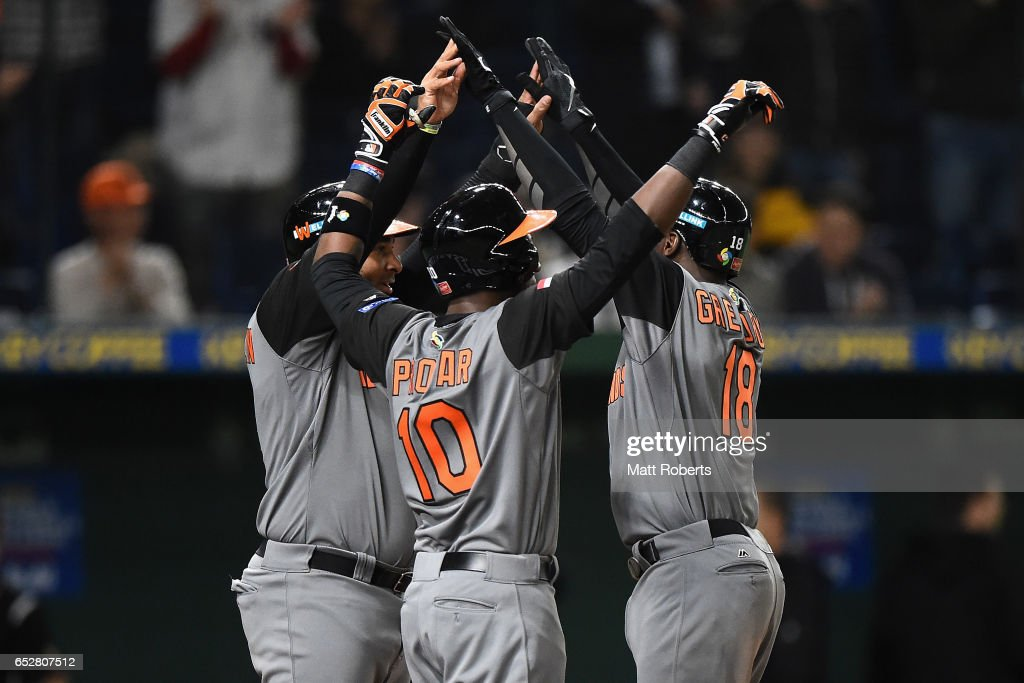 Desingated hitter Didi Gregorius (R) #18 of the Netherlands celebrates with Outfielder Wladimir Balentien (L) #4 and Outfielder Jurickson Profar (C) #10 after hitting a three run homer to make it 10-0 in the top of the fourth inning during the World Baseball Classic Pool E Game Three between Netherlands and Israel at the Tokyo Dome on March 13, 2017 in Tokyo, Japan.