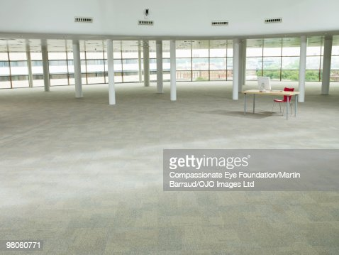 desk and computer in large empty room : Stock Photo
