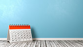 Orange and White Desk Calendar on Wooden Floor Against Blue Wall with Copyspace 3D Illustration