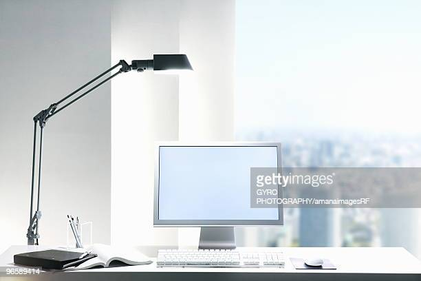 Desk lamp and computer on desk with view of a city through the window