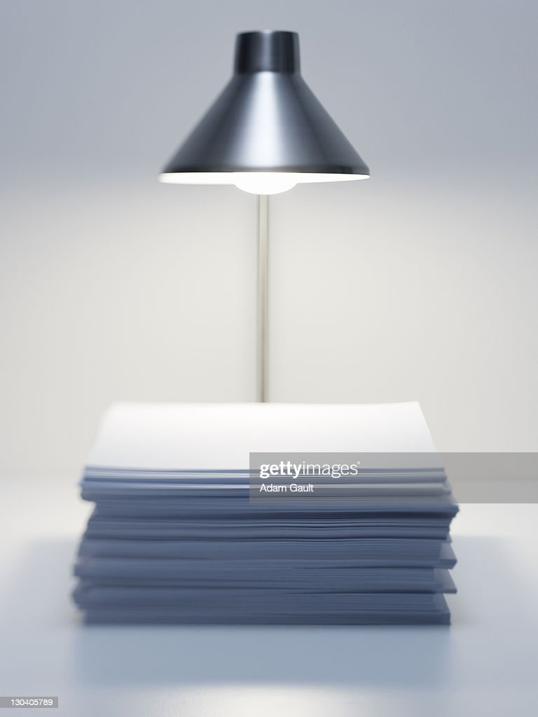 Desk lamp over stack of paper : Stock Photo