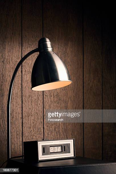 Desk lamp shining down on retro clock against wood paneling